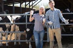 Uomo e donna sorridenti che stanno con nel capannone e lo showin della mucca Fotografie Stock Libere da Diritti