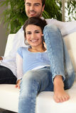 Uomo e donna sorridenti sul telefono su un sofà Fotografie Stock Libere da Diritti