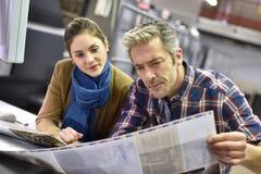 Uomo e donna in stamperia che controllano qualità stampa fotografie stock
