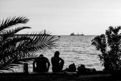 Uomo e donna sulla linea costiera nel porto sull'estremità della conclusione del giorno - gradazione di grigio, granulosa Fotografie Stock Libere da Diritti