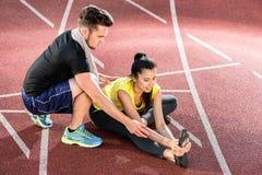 Uomo e donna sulla pista di cenere di allungamento dell'arena di sport Fotografia Stock