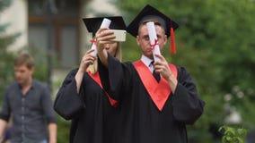 Uomo e donna in vestiti accademici che prendono selfie dopo la graduation stock footage