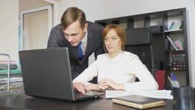 Uomo e donna in vestiti rigorosi sul lavoro sul computer portatile, documenti, discussione nell'ufficio fotografia stock libera da diritti