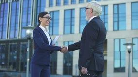 Uomo e donna in vestiti ufficiali che stringono le mani, segno di cooperazione, contratto video d archivio