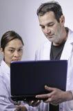 Uomo e donne che esaminano computer portatile. Fotografie Stock Libere da Diritti