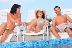 Uomo e donne sorridenti che si adagiano sui salotti del chaise Immagini Stock