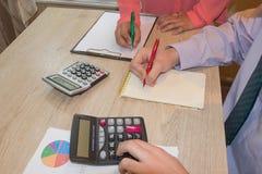 Uomo e femminile, contando soldi ed effettuando i calcoli fotografia stock