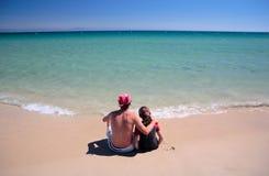 Uomo e figlia che si siedono sulla spiaggia abbandonata piena di sole Fotografie Stock