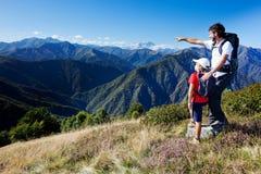 Uomo e giovane ragazzo che si levano in piedi in un prato della montagna Fotografie Stock
