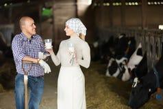 Uomo e lavoratrici agricole che stanno con il latte fresco Immagine Stock