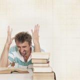 Uomo e libri arrabbiati Fotografia Stock