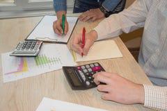 Uomo e mano femminile con il calcolatore all'ufficio del posto di lavoro Immagini Stock