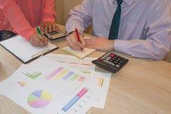 Uomo e mano femminile con il calcolatore all'ufficio del posto di lavoro Immagine Stock