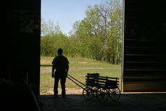 Uomo e piccolo vagone in siluetta fotografia stock