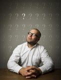 Uomo e punti interrogativi Fotografie Stock