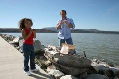 Uomo e ragazza sul riverbank Immagini Stock