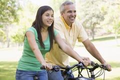 Uomo e ragazza sulle bici all'aperto che sorridono Fotografie Stock Libere da Diritti