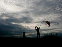 Uomo e ragazzino che pilotano un aquilone al tramonto Fotografia Stock
