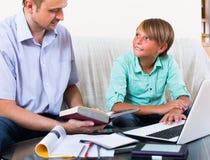 Uomo e ragazzo adulti con il computer portatile all'interno Fotografia Stock