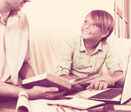 Uomo e ragazzo adulti con il computer portatile all'interno Immagine Stock Libera da Diritti