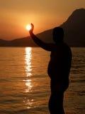 Uomo e sole a sunse sul mare Fotografie Stock Libere da Diritti