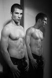 Uomo e specchio muscolari Fotografie Stock Libere da Diritti