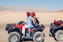 Uomo e sua figlia che conducono la bici del quadrato nel deserto di Sinai Famiglia felice divertendosi durante le vacanze estive fotografia stock libera da diritti