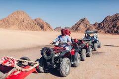 Uomo e sua figlia che conducono la bici del quadrato nel deserto di Sinai Famiglia felice divertendosi durante le vacanze estive fotografie stock libere da diritti