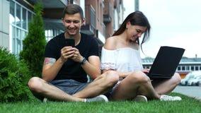 Uomo e una donna che per mezzo di un telefono cellulare e di un computer portatile mentre sedendosi sull'erba stock footage