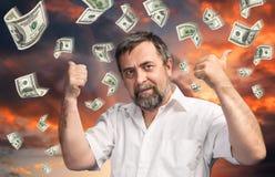 Uomo e una pioggia di 100 banconote in dollari Immagini Stock Libere da Diritti