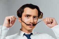 Uomo eccentrico con i baffi lunghi nella suoi camicia e legame Un impiegato di concetto pazzo, un uomo d'affari fotografia stock