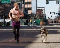 Uomo ed il suo funzionamento del cane Fotografia Stock
