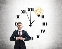 Uomo ed orologio con la lampadina su calcestruzzo Immagine Stock Libera da Diritti