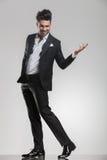 Uomo elegante che cammina mentre tenendo una mano nell'aria Immagini Stock
