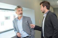 Uomo elegante che parla con collega con gesticolamento fotografia stock libera da diritti