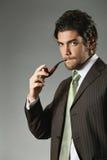 Uomo elegante che posa con un tubo immagine stock