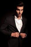 Uomo elegante che sbottona il suoi cappotto e distogliere lo sguardo fotografia stock