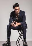 Uomo elegante con i vetri che si siedono sulla sedia Immagini Stock