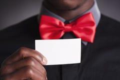 Uomo elegante con il biglietto da visita rosso della tenuta del farfallino Immagini Stock Libere da Diritti