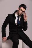 Uomo elegante di affari che si siede su un cubo bianco Fotografia Stock Libera da Diritti