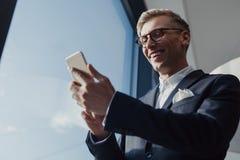 Uomo elegante sorridente che per mezzo dello smartphone Immagini Stock Libere da Diritti