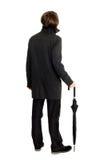 Uomo elegante in un impermeabile che si leva in piedi indietro Fotografia Stock
