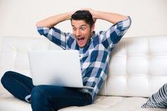 Uomo emozionante che guarda gioco sul computer portatile fotografie stock libere da diritti