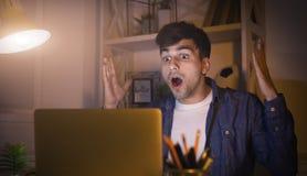 Uomo emozionante che lavora tardi a casa sul computer portatile Fotografia Stock