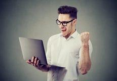 Uomo emozionante con il computer portatile che celebra successo Immagine Stock Libera da Diritti