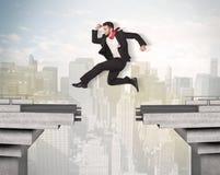 Uomo energetico di affari che salta sopra un ponte con la lacuna Fotografie Stock
