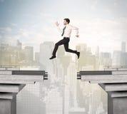 Uomo energetico di affari che salta sopra un ponte con la lacuna Fotografia Stock