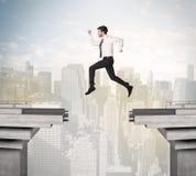 Uomo energetico di affari che salta sopra un ponte con la lacuna Fotografia Stock Libera da Diritti