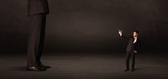 Uomo enorme con il piccolo imprenditore che sta al concetto anteriore Fotografie Stock