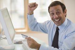Uomo entusiastico che per mezzo della carta di credito e del calcolatore Fotografia Stock Libera da Diritti